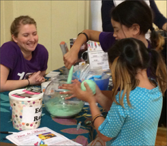 Girls exploring exhibit at program table
